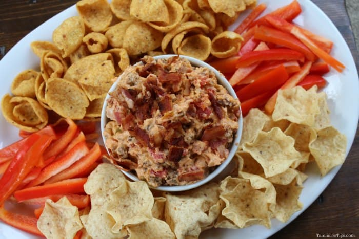 Bacon Cheeseburger Crock Pot Dip in a white bowl surrounded by red bell pepper strips and tortilla chips on a white platter