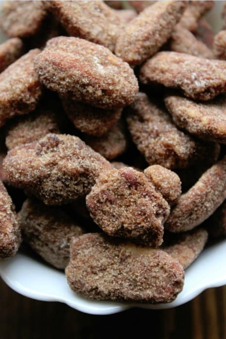 close up of the cinnamon sugar crockpot candied pecans in a white bowl with a brown background.