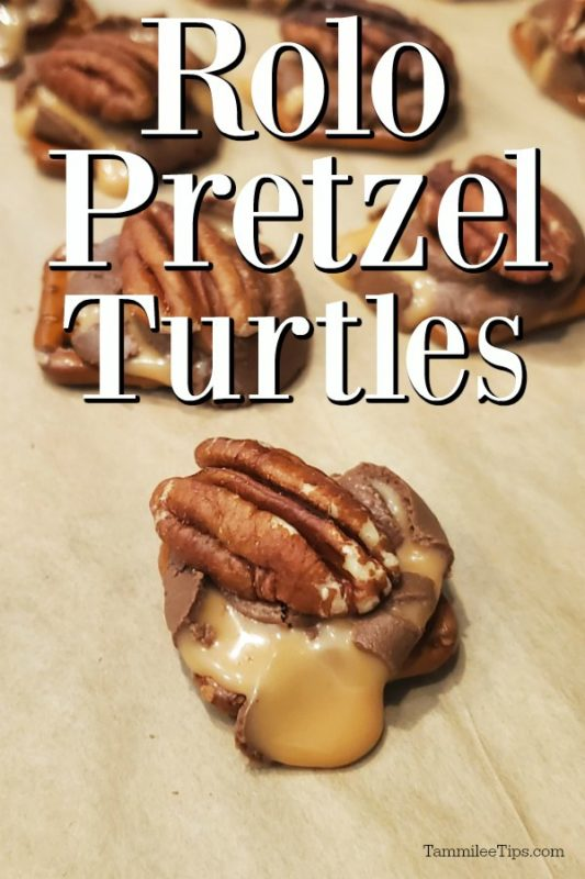 Rolo Pretzel Turtles on parchment paper with caramel coming out over the pretzel, pecan on top