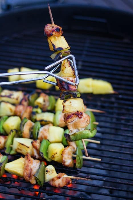 Grilled chicken skewers on a charcoal grill with pineapple and green pepper