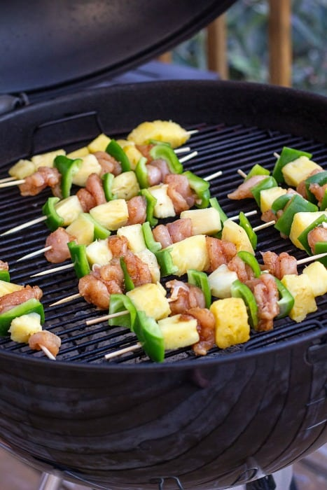 Grilled sweet and spicy chicken skewers on a black barbecue