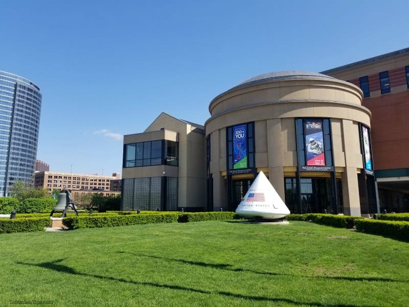 Grand Rapids Museum exterior with green grass lawn, space equipment, and blue skies