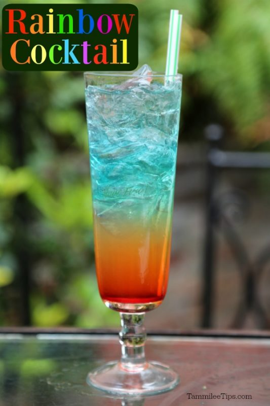 Rainbow cocktail on a table with a green background