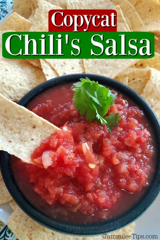 Copycat Chili's Salsa in a black bowl with a tortilla chip in it.
